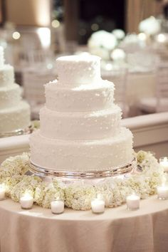 white flowers and candles around a simple cake