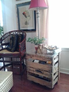 Side table made out of stacked and hinged wine crates placed on casters with locks and topped with a sheet of glass.