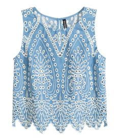 Sleeveless blouse in woven fabric with eyelet embroidery and scalloped trim at hem. Opening at back of neck with button. Slightly shorter style. Unlined.