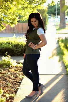 Green army vest, white t-shirt, gray heels
