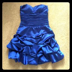 Royal Blue Short Formal Prom/Homecoming Dress Short, strapless prom dress by Dancing Queen with sweetheart neckline, ruched bodice and pick-up skirt. White faux gemstones at the neckline. Worn only once and in great condition with no stains, tears, or other visible signs of wear. It's a beautiful royal blue satin and comes with a matching wrap in the same material (last picture). Willing to negotiate price. Dresses Prom