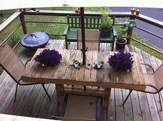 une table en palette et une décoration de fleurs lilas
