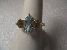 Brand new with tag Sterling Silver Citrine and Blue Topaz Ring, approx 13 x 6 mm Genuine Marquis Cut Blue Topaz and 2 pieces 6 x 6 trillion cut citrine. Weigh 3.7 grams, hallmarked 925, size 7. Comes with original Box , original price $250.