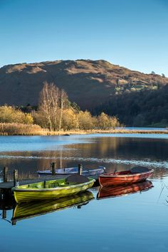 Rowing Boats on Grasmere in the English Lake District, showing three differently coloured rowing boats on still water against a clear blue sky.