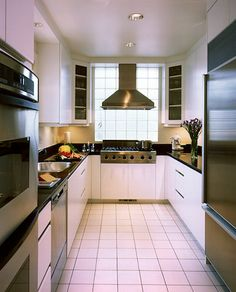To create a U-shaped space, this homeowner closed off one end of a walk-through galley kitchen with a glass-block wall behind the stove.