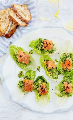 Chunky avocado and smoked salmon boats topped with nigella seeds and a squeeze of lemon - these make delicious canapés for parties!