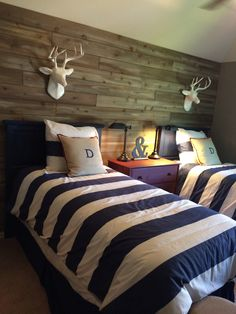 Cute boys room in TX model.  Stripes, double twin beds, deer antlers