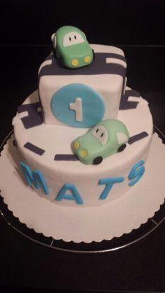 Spielzeugautos aus Fondant zum ersten Geburtstag. Torte mit Schokoladen und Erdbeerfüllung.