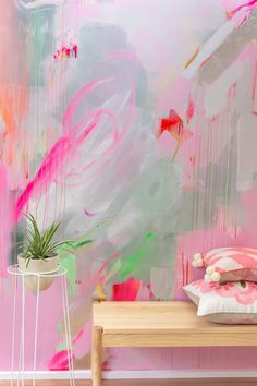 Vibrant abstract mural in pink, red and pastel colours, the energetic brushstrokes resemble a butterfly. A house plant in an Ivy Muse plant stand sits in front of the mural along with two Bonnie and Neil cushions.