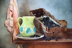 http://pixels.com/products/green-pitcher-and-black-currants-nikolay-panov-art-print.html rustic still life photography with green pitcher, ancient basket full of black currants and old torn towel hanging on the wall in country house in July in summer