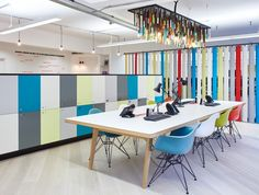 An informal working space with colourful  Eames Dar Chairs