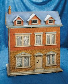 """Lot: 26"""" (66 cm.) German Wooden Two-Story Dollhouse. 26""""h. x 21""""l. The two-story wooden dollhouse has three gabled windows at the roof, faux-brick lithographed paper cover on front and sides, and wooden-framed windows and door at the front, four interior rooms. Good condition, unrestored, some fading and wear. Germany, possibly Gottschalk, circa 1900."""
