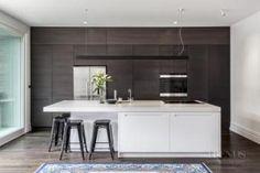 Kitchen renovation combines understated white island with dark wood cabinetry kitchen