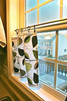 Hang kitchen towels from ring clips for no-sew curtains.  I couldn't find any towels but I did find fabric scraps and iron-on adhesive