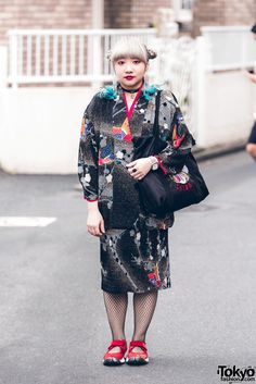 Misaki is wearing a vintage printed coat and matching skirt, fishnet stockings, red Nike Air Rift split toe shoes, and a black satin Chiba tote bag. Her accessories include statement feather earrings, a choker necklace, a watch, and rings.