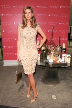 Ivanka Trump in a nude cocktail dress with heraldic floral appliques.