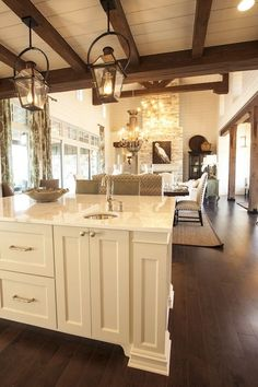 Cottage kitchen with rustic wood beams layered over white plank ceiling. Pair of iron carriage lanterns over white marble top kitchen island and round hammered prep sink with brushed nickel gooseneck faucet. Kitchen opens to dining room and family room.