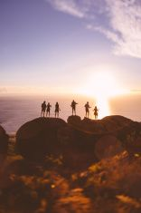 Silhouettes of teens on rocks with sunset over the sea stock photo