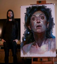 Renato Guedes beside one of his paintings