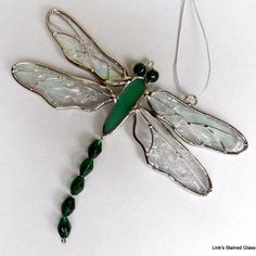 A delightful stained glass green dragonfly suncatcher. An exclusive design by Link& Stained Glass. Made with green glass beads for eyes and tail. Iridescent clear textured wings with wire overlay. Dragonfly Stained Glass, Stained Glass Ornaments, Stained Glass Suncatchers, Faux Stained Glass, Glass Butterfly, Stained Glass Lamps, Stained Glass Designs, Stained Glass Projects, Stained Glass Patterns