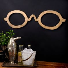 This quirky conversation piece is our spin on a vintage optical trade sign. This is very reminiscent of old turn of the century trade signs that in their day were considered very high tech but now seem quaint. Size: 31 W x 9H x .5 D These over-sized eyeglasses are cut from half inch