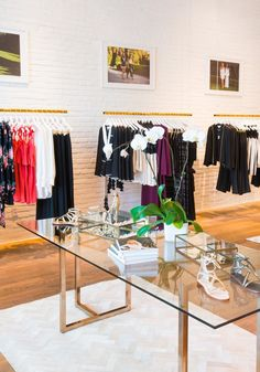 Retail space with gold clothing racks, a modern glass table, and exposed brick