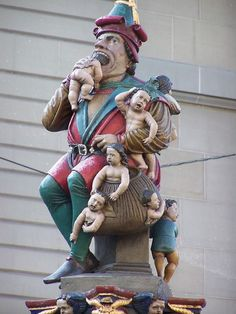 """The Kindlifresser, or """"Child Eater,"""" Bern, Switzerland. Built in 1546, the city's oldest fountain depicts a sculpture of an ogre who has a taste for the babies. One is stuffed in his mouth, while several others await their sad fate."""