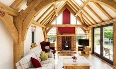 Cosy barn room with exposed oak frame and feature fireplace by Roderick James Architects