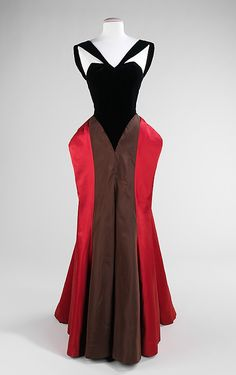 Black, brown, and red silk and wool evening dress (front) by Charles James, American, 1946. The construction of this dress reconfigures the body by having the harder draped fabric brought forward and soft fabric at the back, the opposite from the norm, giving the appearance of front and back being reversed. The startling color contrast and different reflective qualities of satin, wool-backed crepe and faille in the skirt reinforce this deception. The form of the hips bears witness to James' claims of being a sculptor of fabric.