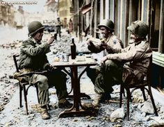 An American version of a sidewalk cafe, in fallen La Haye du Puits, France on July 15, 1944, as Robert McCurty, left, from Newark, New Jersey, Sgt. Harold Smith, of Brush Creek, Tennessee, and Sgt. Richard Bennett, from Wilkes Barre, Pennsylvania, raise their glasses in a toast. -