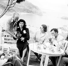 AVA GARDNER in Tossa del Mar, Spain (1950) with composer Jimmy Van Heusen (showing her how to use a Rolleiflex twin-lens camera), Doreen Grant and Frank Sinatra.