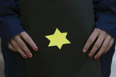HOLOCAUST REMEMBERED--A girl holds a booklet with a yellow Star of David symbolizing the sign identifying Jews during World War II, as Israeli activists hold a ceremony outside the German embassy in Tel Aviv, Israel, on Holocaust Remembrance Day, Thursday, April 19, 2012. Sirens sounded across Israel on Thursday morning, bringing life to a standstill as millions of Israelis observed a moment of silence to honor the memory of the 6 million Jews killed in the Holocaust of World War II.