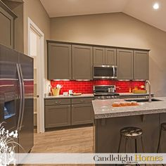 The red backsplash in this kitchen is such a statement! What bold pieces do you love having in your home? Candlelight Homes. Utah Homes. Utah Builder. New Homes Utah. We Build Beautiful. Kitchen. Backsplash. Red Backsplash. Subway Tile. Home Decor. Interior Design. Home. Utah