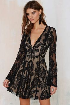 The Romantics Dress is made in black mesh lace and features plunging neckline, bell sleeves, baroque-inspired jacquard embroidery, and raw hemline.