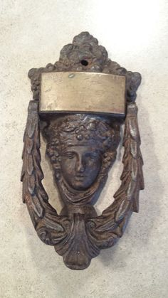 This piece is awesome! From the best I can find, this Wilsons patent (cast iron with brass plate) was found in the United States patent book 1831 - Wow - old stuff! A Cast Iron Door Knocker possibly Grecian womans face. Knocker is surrounded by olive branch leaves. It is very heavy