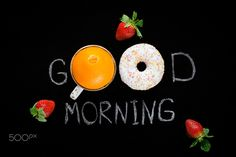 Sweet good morning! - Good morning greeting written on black chalk board. Donut (doughnut), sweet orange and strawberries. Breakfast concept. Flat lay