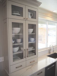 Built in modern dish cabinet Glass front, shaker cabinet, revere pewter, gold hardware, quartz countertops by Daltile, picture window, white dishes, transom cabinets with lighting