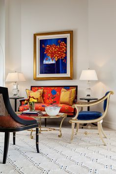 More formal sitting area in this living room features bright floral pattern on the sofa, royal blue velvet on the accent chair and sculptural bronze coffee table.