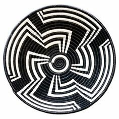 """Lend a touch of worldly appeal to your console or coffee table with this delightful sweetgrass basket, showcasing a tribal motif in black and white.  Product: BasketConstruction Material: SweetgrassColor: Black and whiteFeatures:  Tribal-inspired motifHand-woven using needles and fine plant threadsMade by artisans in  Rwanda Dimensions: 12"""" Diameter x 3"""" Diameter"""