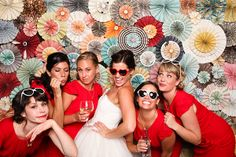 Photo booth DIY backdrop. Paper flowers. Red Bridesmaids. Tea Length Wedding Dress.