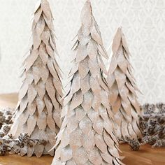Snow-Covered Tabletop Christmas Trees~~The neutral shade of these easy-to-make tabletop Christmas trees will never go out of style. Draw a leaf pattern onto a piece of white paper; cut out. Trace the leaf shape onto thin cardboard and cut out enough pieces to completely cover a papier-mâché cone.