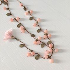 Collana pendente con perline e charms. Chiusura a moschettone.
