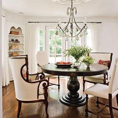 White and Bright Dining Room | Natural lighting makes a dining room magnetic. A clutch of chairs normally found in a living room, including two English wing chairs, amps up this room's style. Canvas upholstery unites the mismatched vintage chairs.
