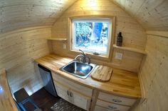 160 sf tiny house kitchen, pic 7. I would need a taller/ larger fridge, so first swap the fridge over to the right of the sink, and the drawers to the left. Add a swing up counter to the wall on the left to help make up for the loss of counter where the fridge is. Add shelves on the left wall, and a deeper shelf for a microwave/convection oven.