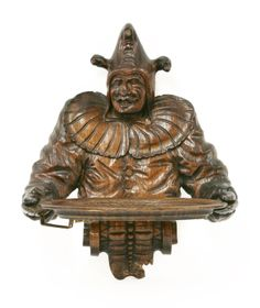 An oak wall shelf, modelled as a grinning jester holding an elliptical tray Est £200-400 4th March 2014