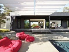 When Prefab Is Painless - Photo 2 of 7 - In the foreground are Float beanbag chairs and poufs from Paola Lenti. Mamagreen sofas nestle near the house on the sun-dappled deck. A 9.5-foot-tall shade cloth curtain seals off the entire length of the house when the couple is away, keeping the heat out of the interior and preventing accidental bird suicides against the floor-to-ceiling glass walls.