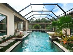 Pool with interesting shape - planters - screen - tropical - courtyard.  Mediterra in Naples, FL