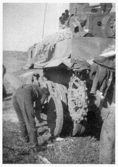 German mechanic in the field, repairing a Tiger tanks wheel suspension system.