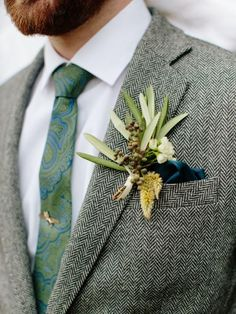 Autumn-Inspired Boutonniere The groom's sage green boutonniere looks playful against a handsome, gray herringbone jacket. A rich teal, satin pocket square and gold tie clip add an extra dose of style to his overall look.
