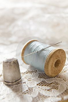 Vintage Cotton Reel With Needle And Silver Thimble On White Lace. I am a sewer and love these little things!